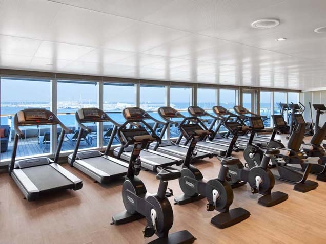 Fitness center - rows of treadmills and cycling machines with mirrored walls and hardwood flooring.