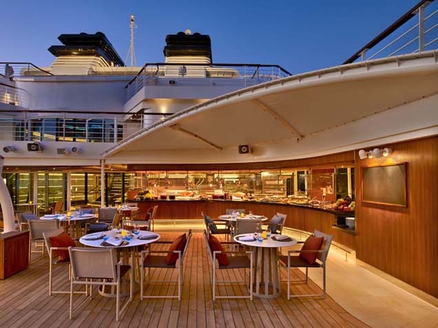 Happy couple seated at Patio bar on deck of Seabourn Odyssey